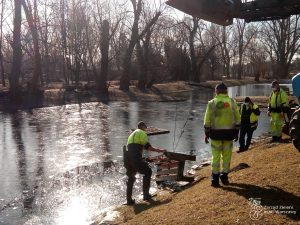 Mężczyźni na tle stawu w Parku Arkadia na Mokotowie - wyciągają betonową ławkę z wody, przy pomocy ciągnika z łyżką.