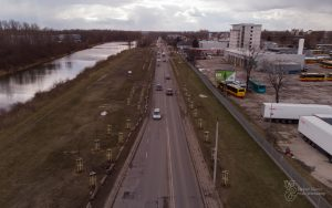 Nowe drzewa w trzech szpalerach przy ul. Płochocińskiej na Białołęce - widok z góry. Po lewej stronie Kanał Żerański, po prawej duży parking. Auta jadą jezdnią.