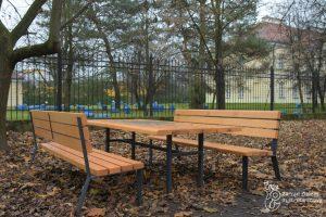 Dwie ławki i stolik w Parku Sieleckim.