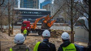 Ciężarówka z przesadzarką drzew wywozi drzewo z Placu Europejskiego, trzech robotników w kaskach przygląda się operacji
