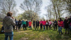 Przyrodnik ZZW Łukasz Poławski opowiada uczestnikom spotkania nad Wisłą o ochronie siedlisk ptaków i lasów łęgowych - stoi przy dużym kamieniu, wokół drzewa