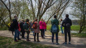 Przyrodnik ZZW Łukasz Poławski opowiada uczestnikom spotkania nad Wisłą o ochronie siedlisk ptaków - stoi przy dużym kamieniu, wokół drzewa