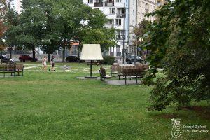 Lampa i półkoliste ławki w Parku Kazimierzowskim, w tle spacerujący ludzie