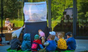 Dzieci biorą udział w warsztatach edukacyjnych w Pawilonie Edukacyjnego Kamień - oglądają teatr cieni